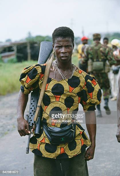 A rebel fighter in Monrovia wears a colorful shirt and holds a rifle during the Liberian Civil War In 1989 Charles Taylor leader of the NPFL launched...