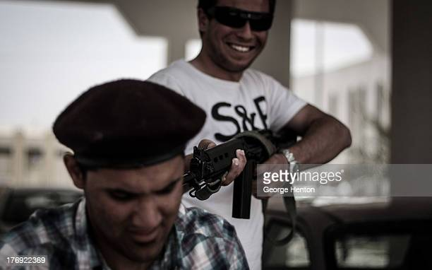 Rebel fighter jokes as he points a rife at the back of the head of a fellow fighter during guard duty at the media centre in Misrata, Libya, 04 June...
