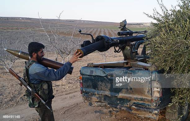 A rebel fighter loads a mortar ahead of firing it towards a proregime position on February 14 2014 at an undisclosed location north of the Syrian...