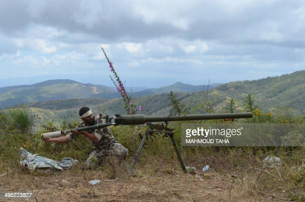 A rebel fighter loads an antitank cannon during fighting against progovernment forces on June 1 2014 on the outskirts of Syria's Mediterranean port...