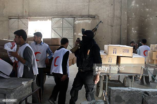 A rebel fighter looks on as workers from the Syrian Red Crescent and United Nations High Commissioner for Refugees unseen arrive with aid at the...