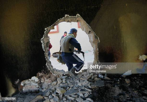 A rebel fighter moves through a hole punched in a wall near the front line fighting on Tripoli Street in downtown Misrata April 18 2011 in Misrata...