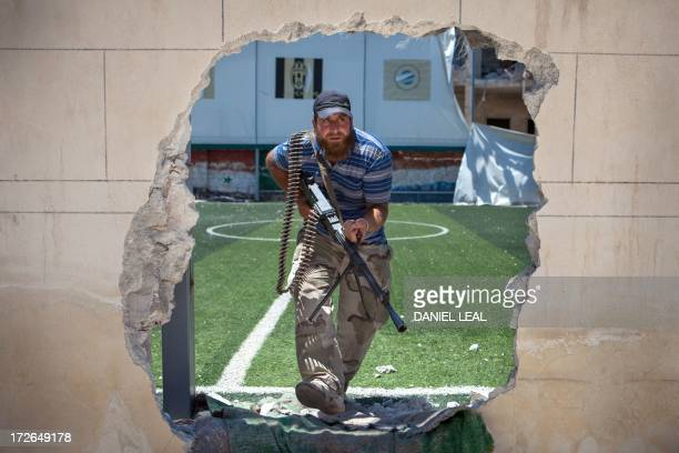 A rebel fighter passes through an access hole broken in the perimeter of a football pitch close to the front line where clashes between the rebels...