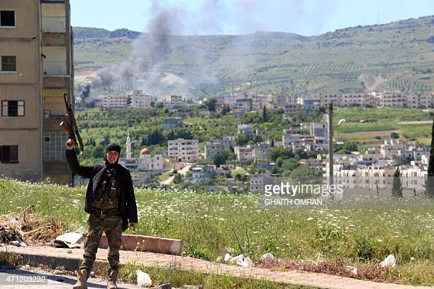 A rebel fighter raises his weapon as smoke billows in the background in the northern Syrian town of Jisr alShughur on April 25 2015 AlQaeda's Syrian...