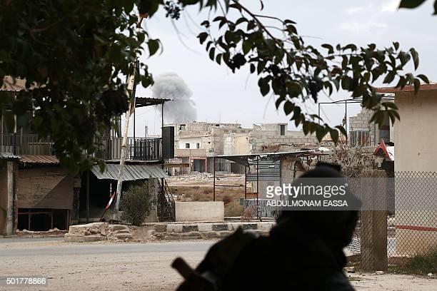 A rebel fighter reportedly belonging to the Faylaq alRahman brigade looks on as smoke billows in the background following a reported air strike by...