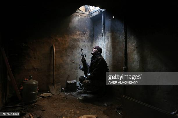 TOPSHOT A rebel fighter reportedly belonging to the Faylaq alRahman brigade looks up from his hiding spot in the rebelcontrolled area of Arbeen on...