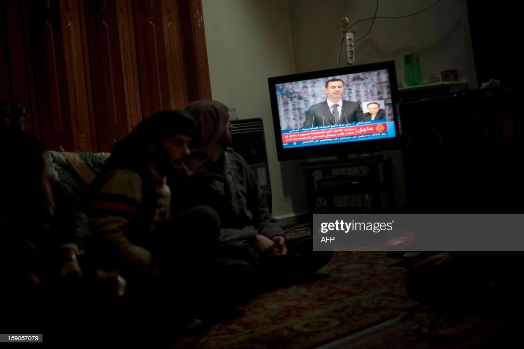 Rebel fighter sit watching Syria's embattled President Bashar al-Assad making a public address on the state-run Syrian TV, on January 6, 2013 in the city of Aleppo. Assad in a rare speech denounced the opposition as 'slaves' of the West and called for a national dialogue conference to be followed by a referendum on a national charter and parliamentary elections.