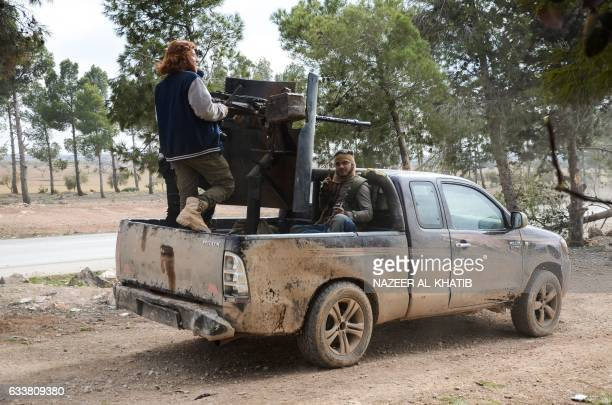 A rebel fighter sits in the back of an armoured pickup truck while another one stands opposite to him as he mans a mounted machine gun near the town...