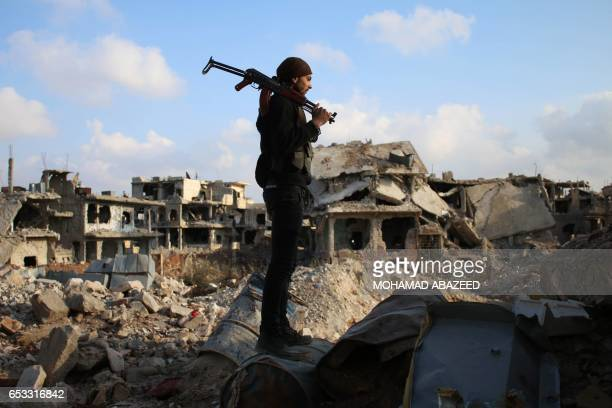 TOPSHOT A rebel fighter stands amid the rubble of destroyed buildings in the rebelheld area of Daraa in southern Syria on March 14 2017 / AFP PHOTO /...
