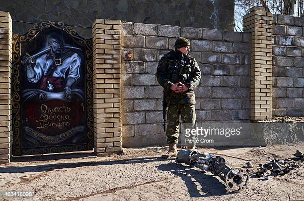 A rebel fighter stands guard at the entrance of the Cossack base near the remains of a missile as fighting continues in the area on February 14 2015...