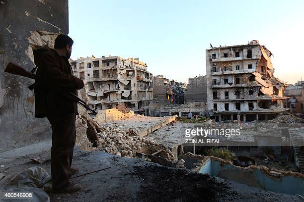 A rebel fighter stands in a building overlooking the damage from fighting in the city of Aleppo on December 16 2013 The EU backed UN efforts to...