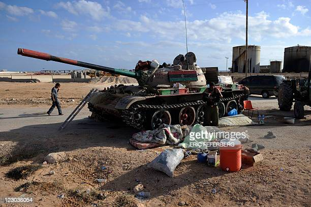 A rebel fighter wakes up near his tank painted with the colours of the new flag of Libya in the eastern town of Bin Jawad on August 30 some 100...