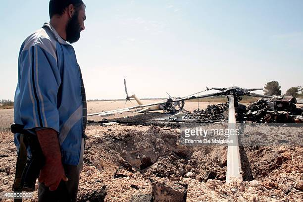 A rebel fighter walks by the charred debris of a gunship helicopter destroyed by NATO air strikes in March 2011 on Misrata airport 28 May 2011