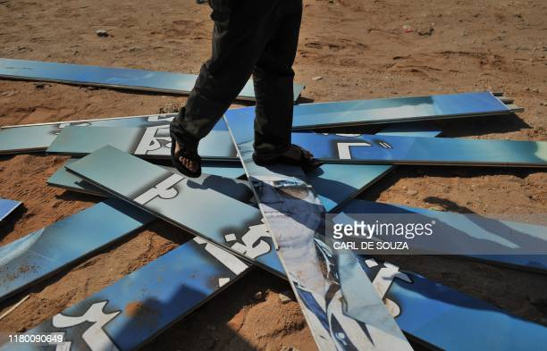 Rebel fighter walks on a destroyed billboard sign with the face of Colonel Kadhafi in Ras Jdir, West Libya on August 27, 2011. Last night Ras Jdir,...