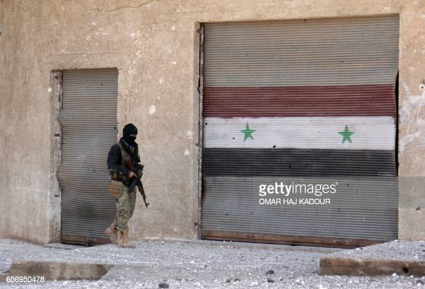TOPSHOT A rebel fighter walks past a roller shutter bearing the Syrian flag in the village of Rahbet Khattab in the Hama province on March 23 2017...