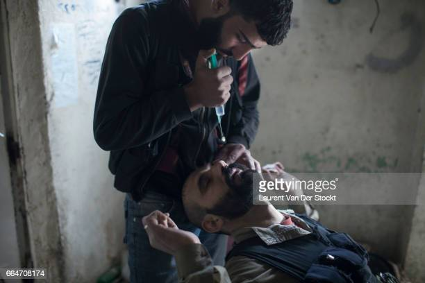 A rebel fighter with Liwa Tahrir al Sham receive prednisolone acetate in eye drops to treat their exposure to sarin gas earlier that week in Jobar a...
