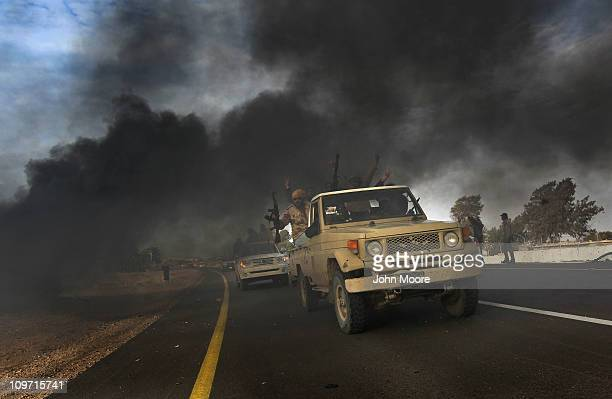 Rebel fighters advance on the front line against Libyan government forces on March 2, 2011 in al-Brega, Libya. The rebels drove out troops loyal to...