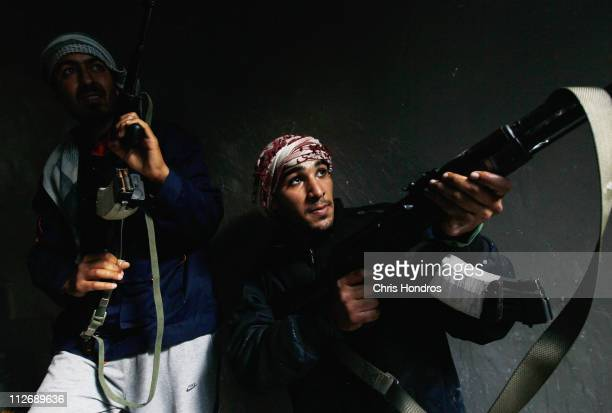 Rebel fighters carefully move into a building where they had trapped government loyalist troops during street fighting on Tripoli Street in downtown...