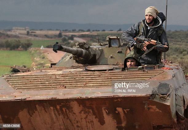 Rebel fighters drive a tank near the frontline in the village of Ratyan in the countryside north of the Syrian city of Aleppo on February 19 2015...
