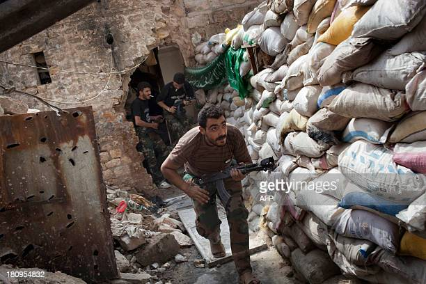 Rebel fighters duck as they run behind a barricade to avoid being fired at by Syrian regime forces in the Old City's front line in Aleppo on...