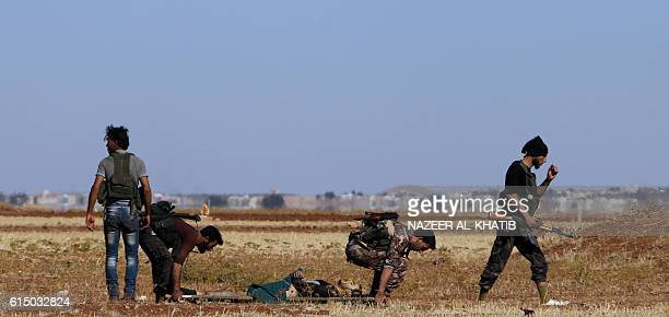 Rebel fighters evacuate a wounded comrade in the village of Tilalayn on the western outskirts of the northern Syrian town of Dabiq on October 16 2016...
