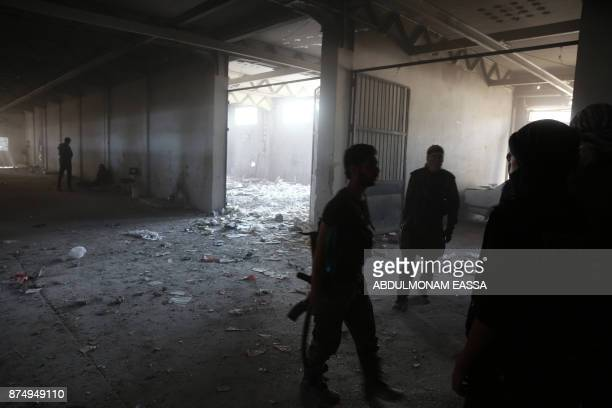 Rebel fighters from the Ahrar alSham brigade inspect the interior of a damaged building in the rebelheld besieged town of Harasta in the Eastern...