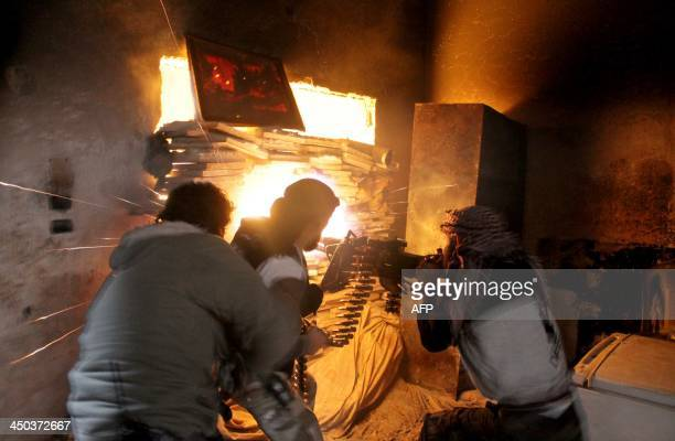 Rebel fighters from the Free Syrian Army fire a heavy machine gun during fighting against government forces on November 18 2013 in the Salah alDin...