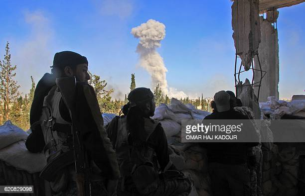 TOPSHOT Rebel fighters from the Jaish alFatah brigades watch as smoke billows in the background on November 3 at an entrance to Aleppo in the...