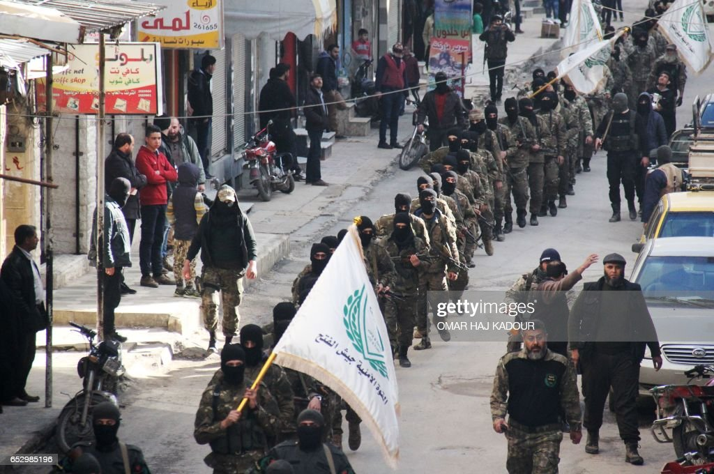 Rebel fighters from the Jaish al-Fatah (or Army of Conquest) brigades, which include other rebel factions, march during a parade in the northwestern Syrian city of Idlib on March 13, 2017. / AFP PHOTO / Omar haj kadour