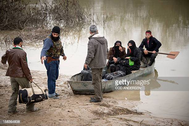 Rebel fighters help two Syrian women load the boat to cross the Orontes river to Turkey near the northern Syrian town of Darkush on December 14 2012...