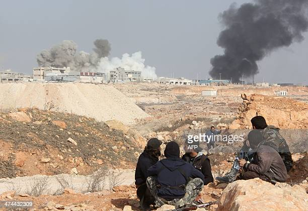 Rebel fighters hold a position as smoke billows in the background during reported battles against progovernment forces on February 23 in the Sheikh...
