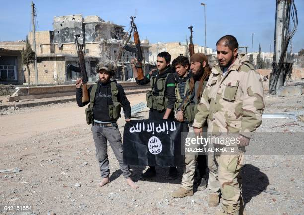 Rebel fighters part of the Turkeybacked Euphrates Shield alliance pose with an Islamic State group flag as they advance on February 20 towards the...