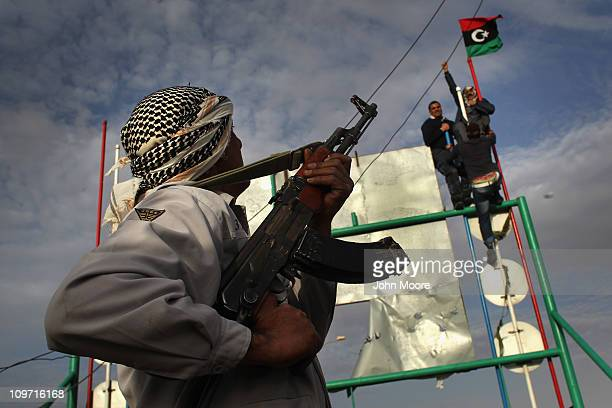 Rebel fighters raise their flag after advancing on the front line against Libyan government forces on March 2, 2011 in al-Brega, Libya. The rebels...