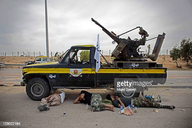 Rebel fighters rest and wait for their orders from the commander on October 9, 2011 in Sirte, Libya. National Transitional Council fighters say this...