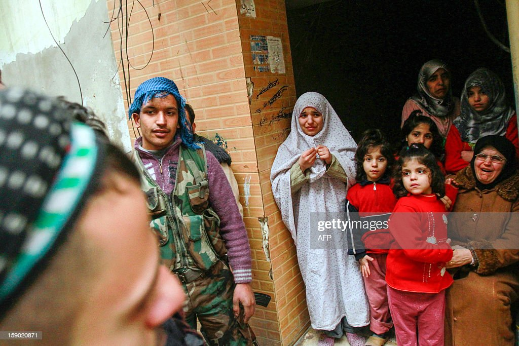 Rebel fighters talk with a family trapped and awaiting their father's return home, along the front line in Salaheddine neighbourhood of Aleppo on January 5, 2013