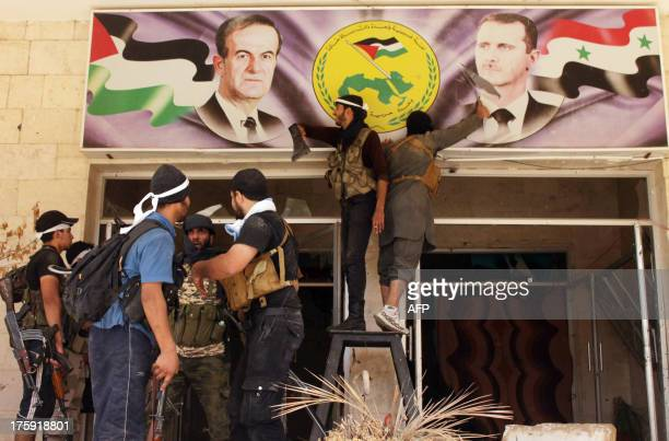 Rebel fighters tear down a poster bearing the portrait of Syrian President Bashar al-Assad and his late father and predecessor Hafez al-Assad in...