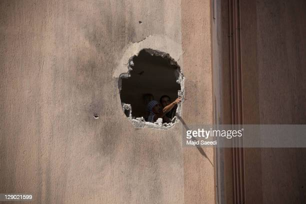 Rebel fighters try to find snipers as they look through a large hole in a building during a street battle in the 700 complex area on October 9 2011...