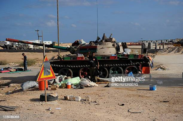 Rebel fighters wake up near a tank painted with the colours of the new flag of Libya in the eastern town of Bin Jawad on August 30 some 100...