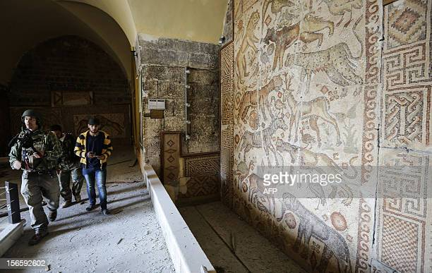 Rebel fighters walk inside the grounds of the alMaraa museum said to be the third largest museum of Romanera mozaics in the world in the town of...