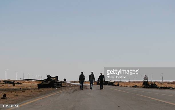 Rebel fighters walk up a desert road near destroyed Libyan army tanks that that had previously been hit by NATO airstrikes April 12 2011 near the...