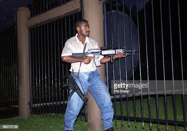 A rebel gunman guards the compound just before a press conference at the Fiji parliament building in the capital Suva after gun shots were fired as...