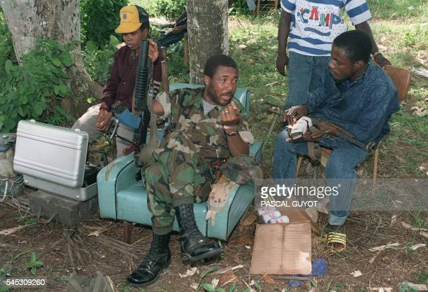 Rebel leader Charles Taylor speaks with troops 21 July 1990 in Roberts Field after taking over this position from government troops of President...