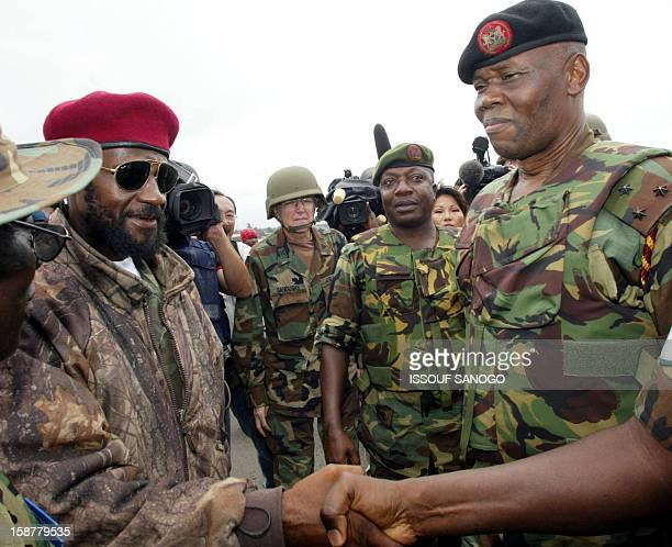 rebel leader Sheriff Seyea shakes the hand of an unidentified person under the eyes of Nigerian General Festus Okonkwo Commandant of the ECOMIL prior...