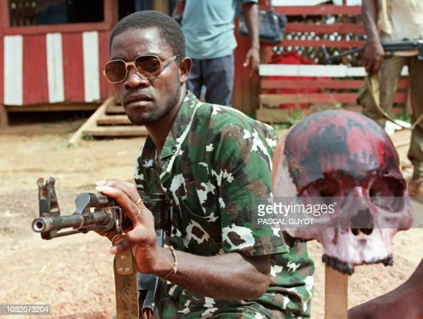 A rebel loyal to the warlord Charles Taylor holding Kalashnikov poses next to a painted scull of a Krahn ethnic soldier of president Samuel Doe 15...