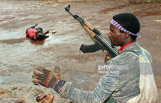 A rebel loyal to warlord Charles Taylor of the National Patriotic Front of Liberia holding a rifle stands in front of a victim killed 10 July 1990 in...
