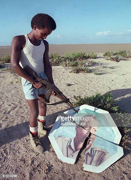 A rebel militiaman belonging to the Somali National Movement fighting the regime of dictator Mohamed Siad Barre points his gun towards the broken...