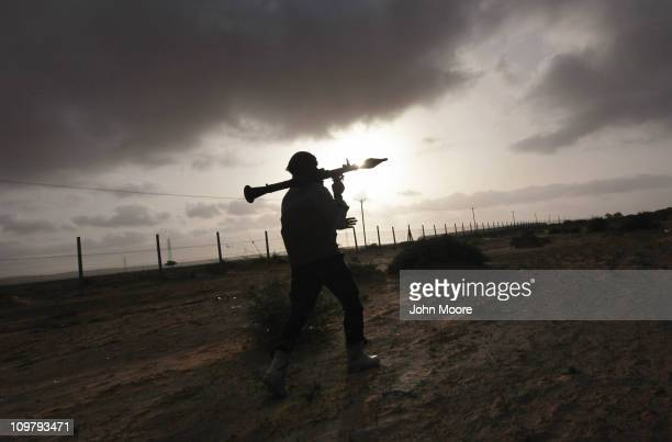 Rebel militiaman carries a rocket propelled grenade while advancing on the frontline March 25 2011 in Ben Jawat, Libya. Opposition forces pushed...