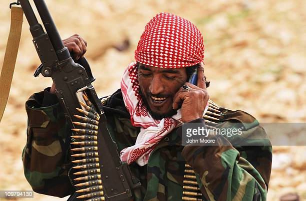 A rebel militiaman speaks on his mobile phone after capturing territory from government troops March 25 2011 in Ben Jawat Libya Opposition forces...