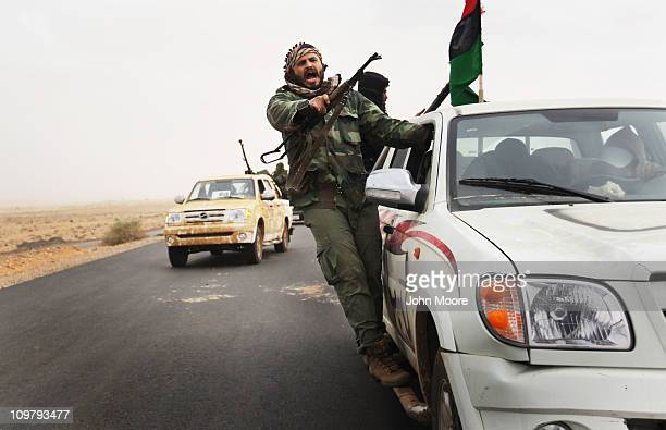 Rebel militiamen advance on the frontline against government troops March 25 2011 in Ben Jawat, Libya. Opposition forces pushed troops loyal to...