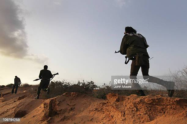 Rebel militiamen advance on the frontline against government troops on March 25 2011 in Ben Jawat Libya Opposition forces pushed troops loyal to...